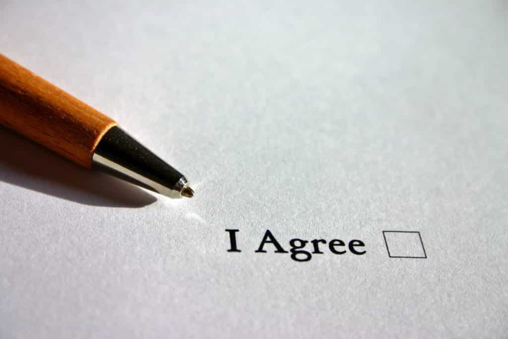 "A pen beside the checkbox with the words ""I Agree""."